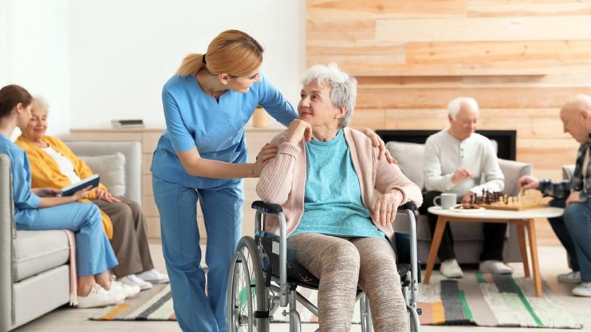 Foto de banco de imágenes que muestra personas mayores y sus cuidadores en un hogar de retiro