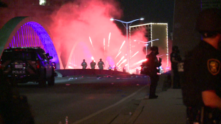 Protesters who were undeterred by tear gas and flashbangs continued to throw frozen water bottles and fire polytechnics towards officers along the West 7th Street Bridge in Fort Worth Sunday night.