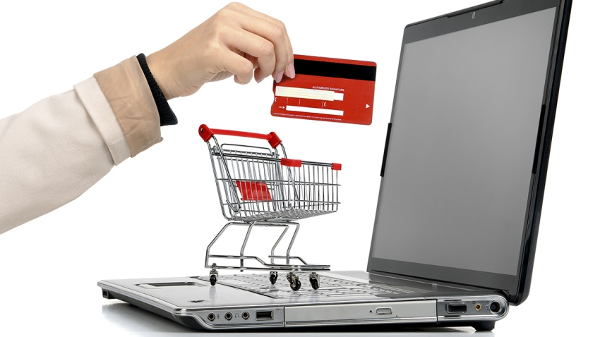 A laptop computer, a grocery cart and a hand holding a gift card.
