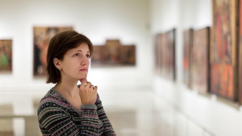 Mujer mirando obras de arte.