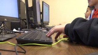 ninos tomando clases en la computadora.