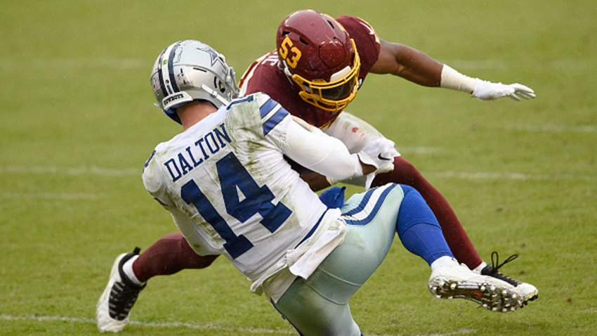 Quarterback Andy Dalton #14 of the Dallas Cowboys is hit and injured by Jon Bostic #53 of the Washington Football Team in the third quarter of the game at FedExField on Oct. 25, 2020 in Landover, Maryland.