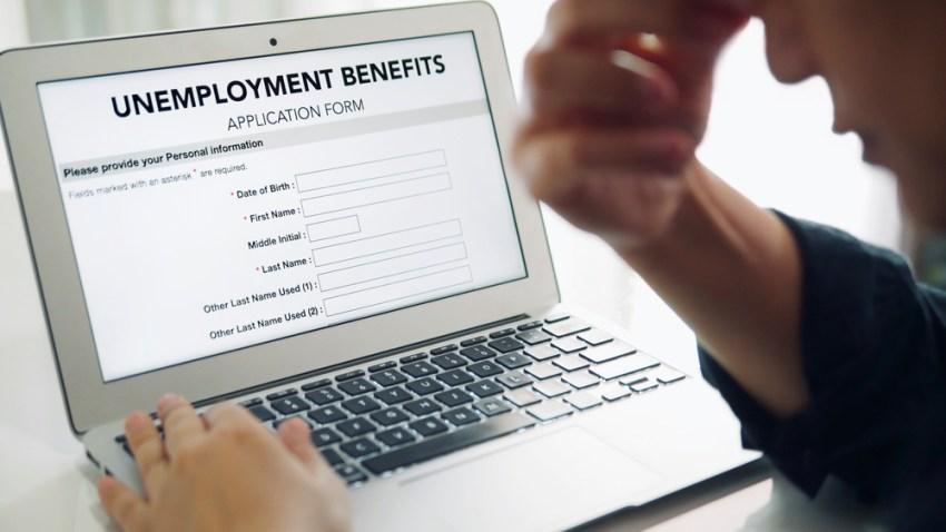Persona frente a una computadora rellenando solicitud de ayuda por desempleo.