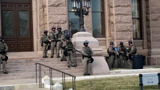 More than 100 Texas troopers, including dozens wearing tactical vests and carrying riot gear, stood on guard outside the state Capitol on Tuesday as lawmakers returned to work amid FBI warnings of armed protests at statehouses across the country.