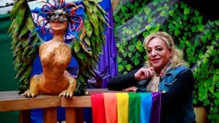 Figura de un alebrije, figura fantástica típica de México y la bandera de la comunidad LGBT acompañan a una de las candidatas a diputada federal