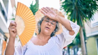 Middle,Age,Woman,With,Grey,Hair,Using,Handfan,On,A