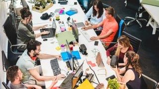 Empleados trabajando en sus computadoras en la oficina.