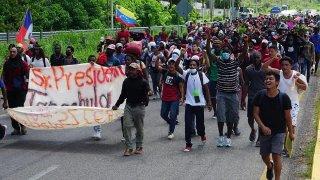 Imagen que muestra a un grupo numeroso de personas migrantes que forman una caravana, no se perciben sus rostros, pero los que van hasta adelante llevan una pancarta con un mensaje que no se aprecia porque está doblada, y se ven algunas banderas de sus países de origen.